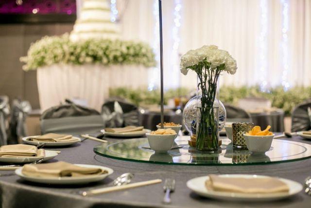 un tavolo apparecchiato con delle ciotole di salatini e un vaso di fiori