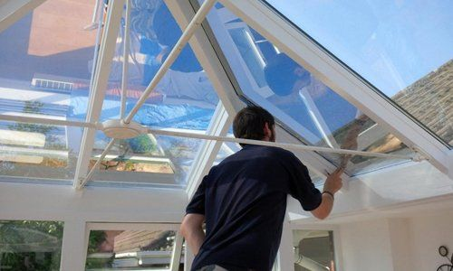man applying window film