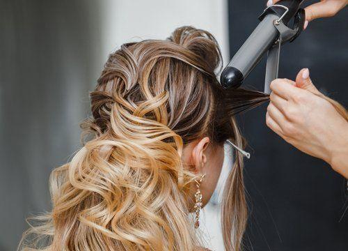 parrucchiera che arriccia i capelli di una donna