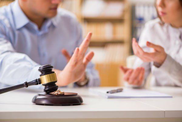 martello da giudice con accanto due fedi matrimoniali. Sullo sfondo un uomo e una donna che discutono.