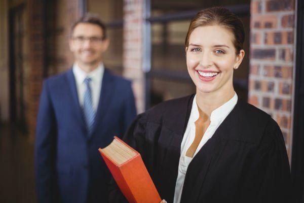 Donna sorridente con toga di avvocato. Uomo sullo sfondo.