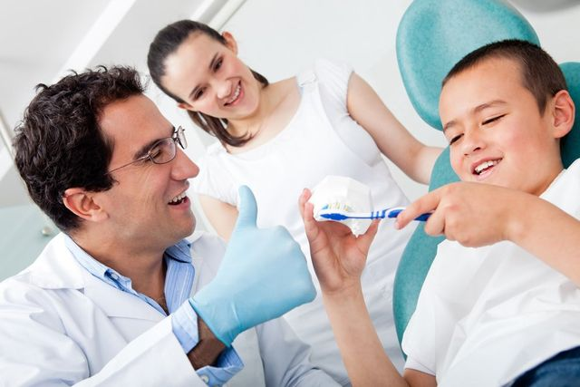 A dentist handing a child a new toothbrush