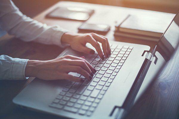 Mani di donna che scrivono al computer