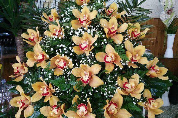 Centro fatto con le orchidee gialle, fiori selvatici bianche e felci