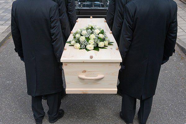 Sei uomini portando la bara coperta da un semplice centro di rose bianche