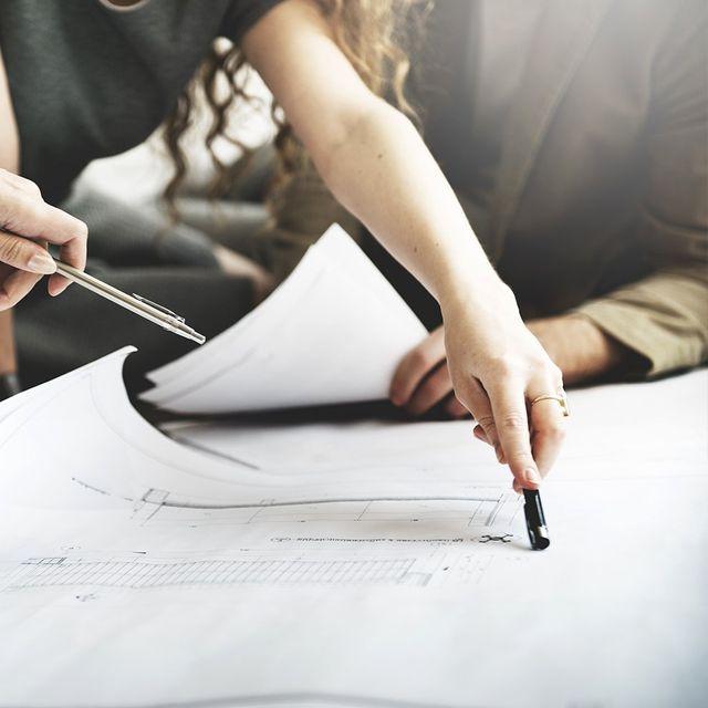 una mano di una donna con una penna in mano che indica un documento sul tavolo