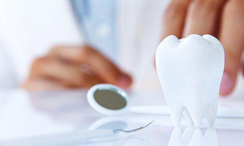 un dente in ceramica, uno specchietto e dietro l'immagine sbiadita di due mani di un dentista con il camice bianco