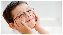 bambino con occhiali da vista sorride tenendosi le guancie