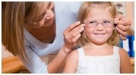 donna mette degli occhiali a una bambina