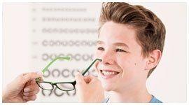 bambino sorride mentre una persona gli mette degli occhiali da vista
