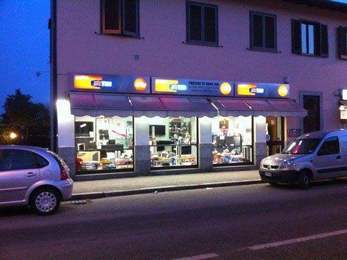 esterno del negozio PASTORE TV VIDEO HI FI, insegna luminosa telefonia mobile Vigevano