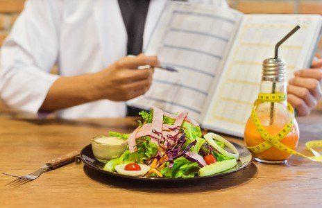 un uomo che punta una penna su un libro e un piatto di insalata sul tavolo