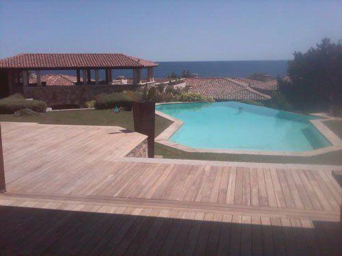 vista di una casa e di una piscina con pavimentazione in liste di legno attorno
