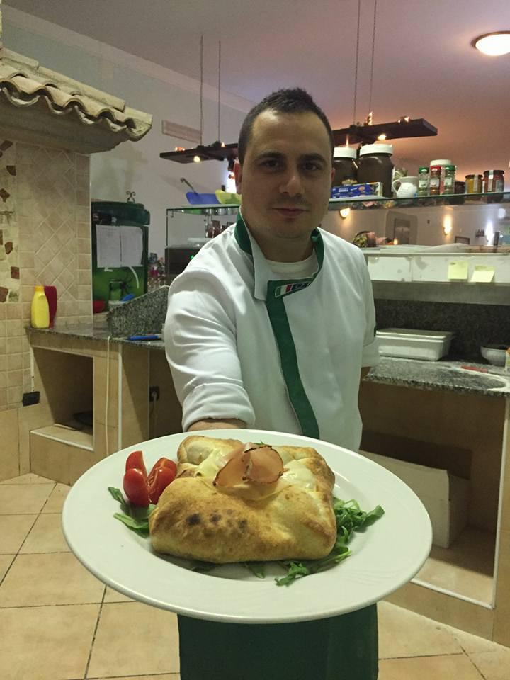 pizzaiolo con in mano un piatto con un calzone a Pignataro Maggiore