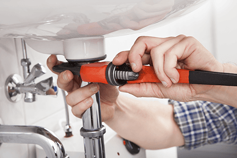 A close up of a plumber working underneath a sink