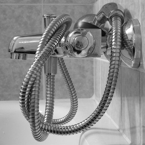 A large shower head with the pipe wrapped around the tap
