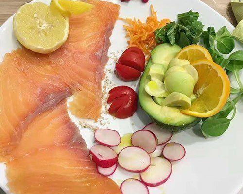 un piatto con carpaccio di salmone,rapanelli,pomodori e altra verdura