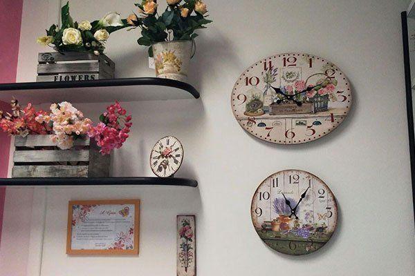 due orologi appesi al muro e mensole di vetro con sopra vasi di fiori