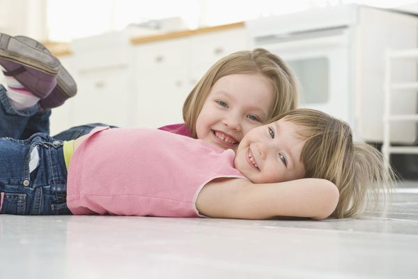 Little girls laying on clean kitchen floor after our complete pest control services in Wailuku, HI