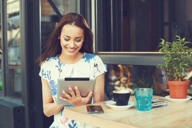 Girl smiling at coffee shop on tablet