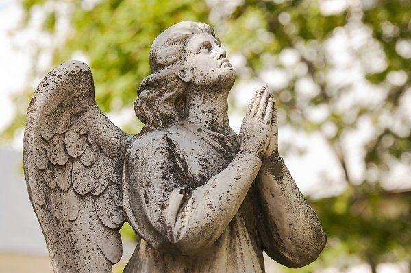 una statua di un angelo che prega