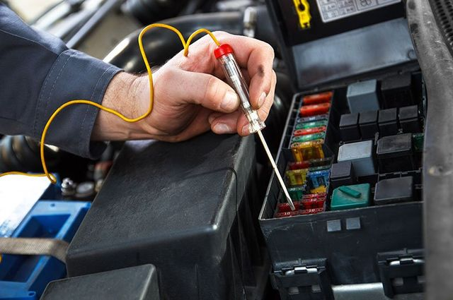 la mano di un meccanico con un cacciavite tester in mano mentre controlla una batteria di una macchina