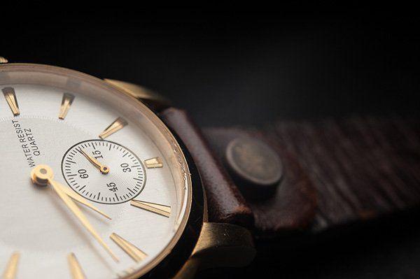 Primo piano di un orologio da uomo d'oro con cinturino di cuoio