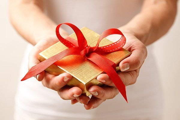 Pacchetto regalo dorato con fiocco rosso