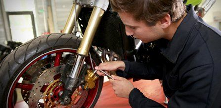 Technician working on motorcycle braking system