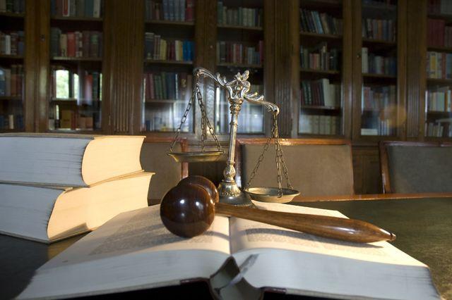 una bilancia a due piatti che pende dal lato destro, un libro aperto e sopra un martello di legno e sulla sinistra altri due grandi libri