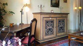 stanza studio con scrivania e sedia in un angolo e mobiletto decorato