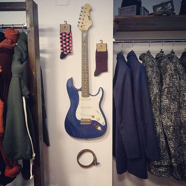 Una colonna con un chitarra blu, delle calze appese con dei ganci, due appendiabiti appesi sui lati con delle giacche di colore blu, bianco e nero