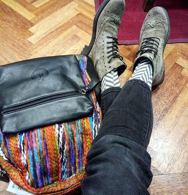 Gambe di un machino seduto sul parquet con dei jeans neri, scarpe di pelle e vicino una borsa nera