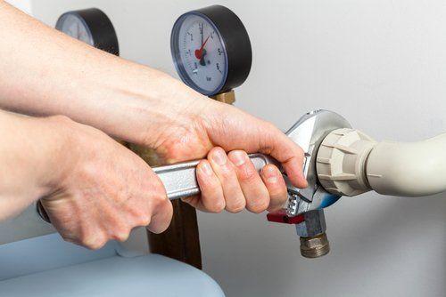 tecnico che ripara tubo con chiave inglese