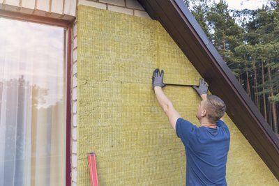 Operaio applica pannelli isolanti sulle pareti esterne di una casa