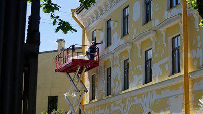 Imbianchino su trabattello decora pareti esterne di un edificio