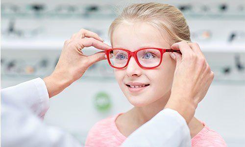 una bambina bionda con degli occhiali da vista rossi durante una visita