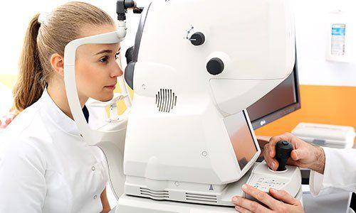 una bambina con capelli castani con la coda durante una visita specialistica con un macchinario di diagnostica oculistica
