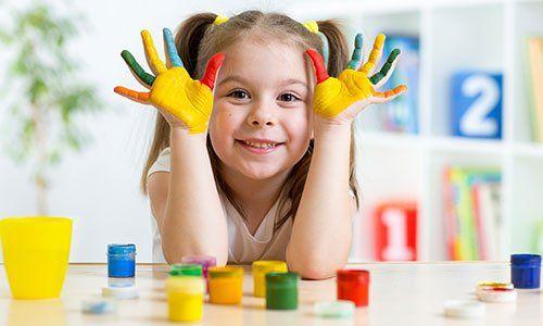 Una bambina sta mostrando i palmi delle mani con su dei colori, seduta a tavola con dei scatoline di colori