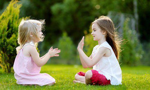 Due bambine sedute nel prato mentre giocano, una batte le mani e l'altra a le mani protese