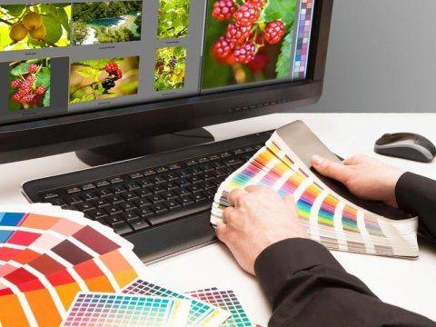 due mani con in mano dei fogli con degli esempi di colore e di fronte una tastiera e un monitor con delle immagini