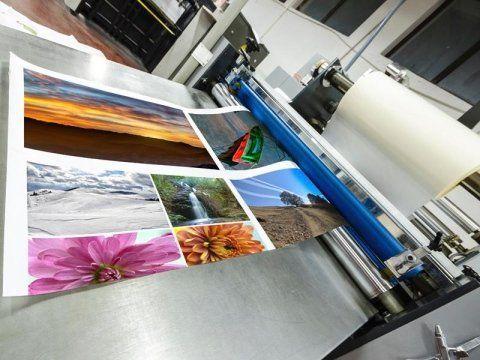 una stampante con dei rulli da dove escono delle immagini stampate su n grande foglio