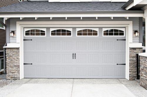 Porta di garage di colore grigio con finestre nella parte superiore