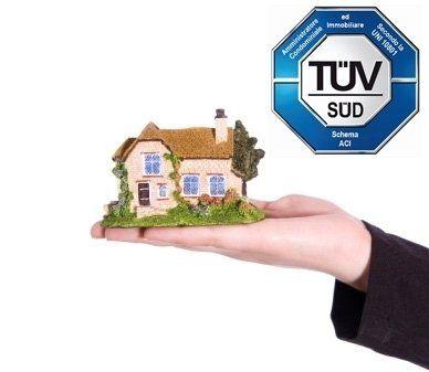 mano che tiene una casa sul palmo e certificazione UNI