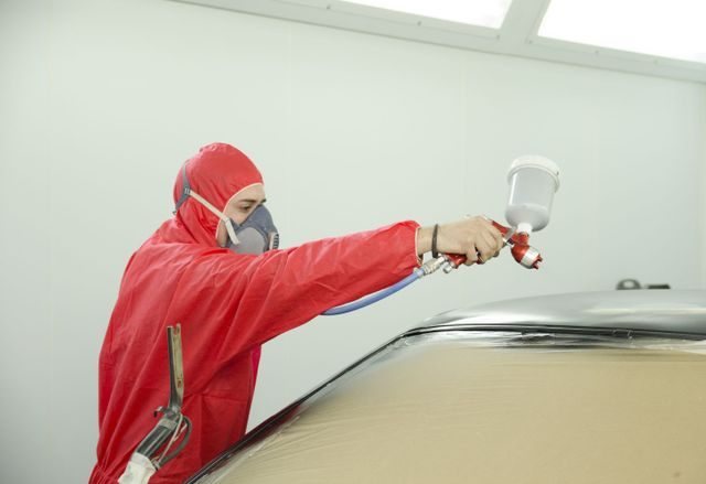 Dent removal specialist spraying new paint in Wailuku, HI