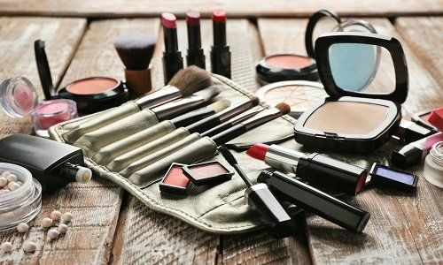 Bossolo con diversi pennelli per il trucco, fard, brillantezza di labbra, rossetto e diversi tipi di trucco