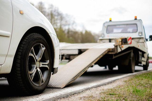 Caricamento auto rotto su un carro attrezzi su una strada