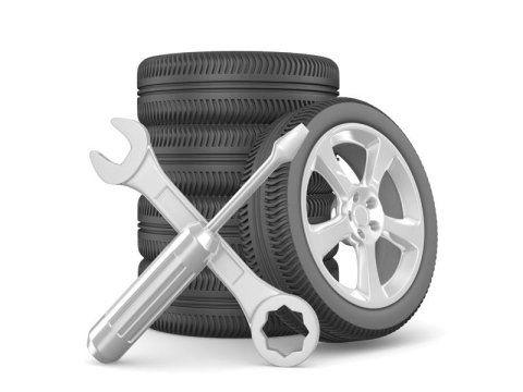 pila di pneumatici con chiave inglese e cacciavite