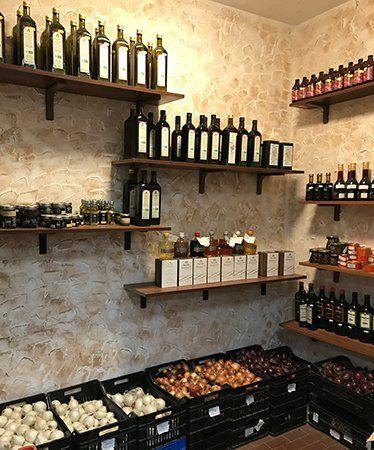 Angolo del business in cui vi sono cassetti con aglio,cipolle, scaffali con diverse varietà di olio e aceto e vari prodotti in imballaggi preconfezionati