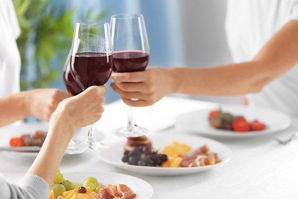 tre persone a tavola con dei piatti mentre brindano con dei bicchieri di vino rosso